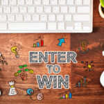 Enter to Win concept with workstation on a wooden desk